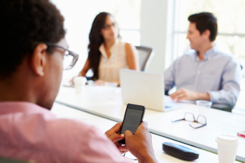 Designer Using Mobile Phone During Meeting